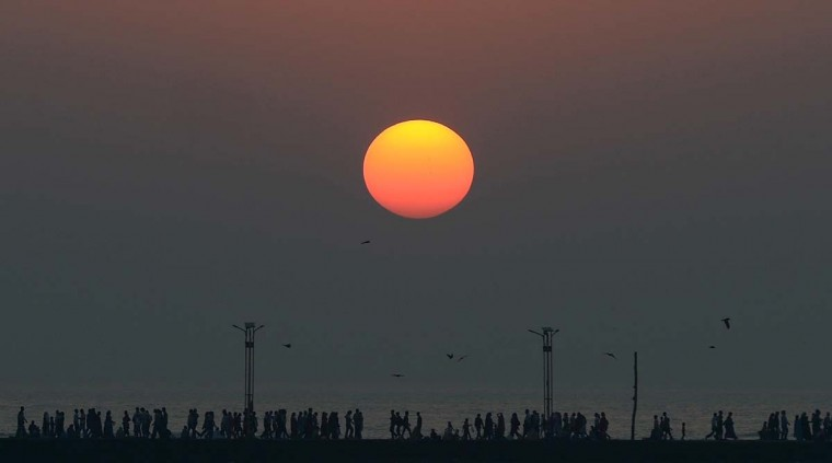 Indian pedestrians walk as the sun sets near the Haji Ali mosque in Mumbai on January 14, 2013. India is part of a global trend that is advancing towards an increasing urbanisation, according to which more than half of the world's population is living in towns and cities. (Punit Paranjpe/AFP/Getty Images)