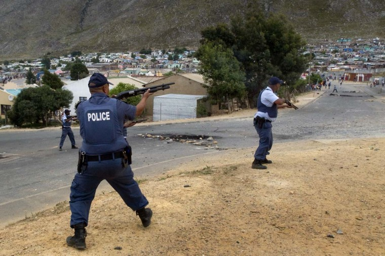 Members of the South African Police Services fire rubber bullets at rock-throwing protestors during an illegal strike by farmworkers, on January 14, 2012 in Villiersdorp, a small farming town about 100Km North of Cape Town, South Africa. The farm workers have said that they they will not return to work on the fruit growing region's farms until they receive a daily wage of at least R150 ($17) per day. (Rodger Bosch/AFP/Getty Images)