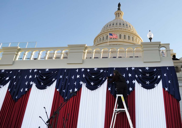 A worker adjusts flags on the U.S. Capitol as preparations continue for the second inauguration of U.S. President Barack Obama in Washington on January 18, 2013. (Jewel Samad/AFP/Getty Images)