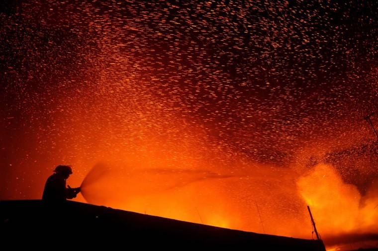 A firefighter attempts to extinguish a fire that engulfed a residential area in Manila on January 19, 2013. Almost 50 houses were destroyed leaving a hundred families homeless, according to local media reports. (Noel Celis/AFP/Getty Images)