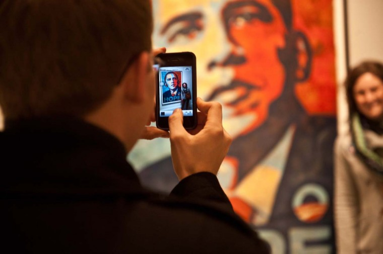 A man takes a picture of his wife standing next to Shepard Fairey's portrait of U.S. President Barack Obama, based on a photograph by Mannie Garcia, at the National Portrait Gallery in Washington on January 19, 2013, two days before Obama's second inauguration. (Nicholas Kamm/AFP/Getty Images)