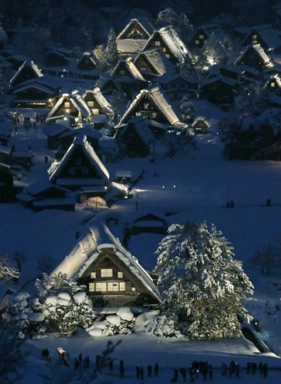 "Japanese traditional wooden houses ""Gassho zukuri"", are lit up in the snow-covered village of Shirakawa in Gifu prefecture, central Japan on January 19, 2013. The Gassho zukuri farmhouses were listed as one of the World Heritage by UNESCO in 1995, and the village will be illuminated until February 16. (JiJi Press/AFP/Getty Images)"