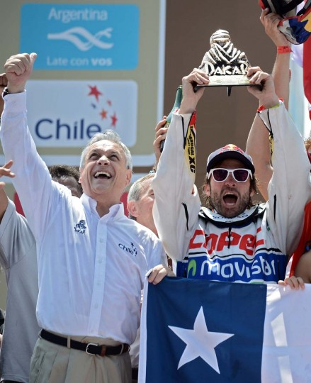 KTM's rider Francisco Chaleco Lopez (R) of Chile celebrates with his trophy next to Chilean President Sebastian Pinera on the podium of the Dakar 2013 in Santiago, Chile on January 20, 2013. KTM's rider French Cyril Despres won the Dakar 2013 ahead of KTM's rider Ruben Faria of Portugal KTM's rider Francisco Chaleco Lopez of Chile. (Franck Fife/AFP/Getty Images)