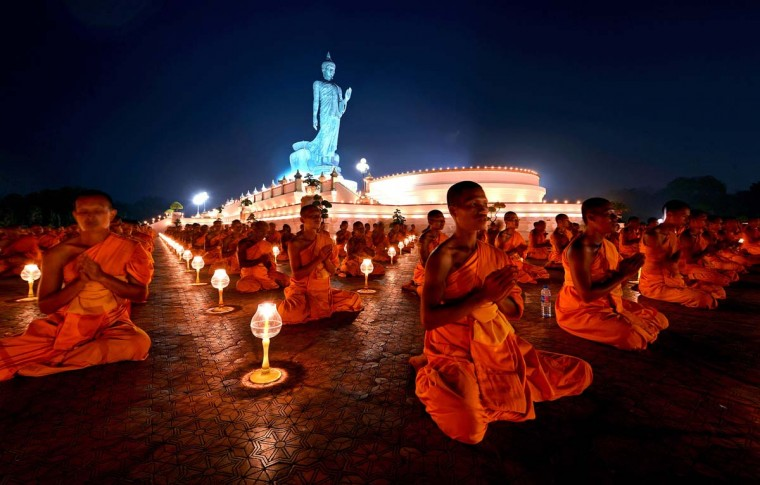Thai and foreign Buddhist monks light candles while chanting at Buddhamonthon in Nakorn Pathom province on January 22, 2013. 1,128 Buddhist monks from Dhammakaya temple lit candles in homage of Lord Buddha. (Pornchai Kittiwongsaul/AFP/Getty Images)