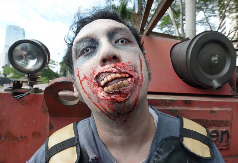 A member of the Indonesian Zombie Club (IZOC) dressed up as a zombie smiles before taking part in a march in Jakarta on January 27, 2013. Hundreds of members of the club took part in a rally intended to raise awareness of cleanness and collected donations for Jakarta residents affected by recent floods. (Adek Berry/AFP/Getty Images)
