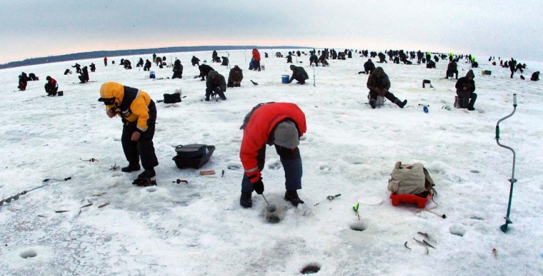 Fishermen stand on the frozen surface of the Kursiai Lagoon near Klaipeda, Lithuania, to catch smelts on January 27, 2013. Several thousands of amateur fishermen from all over Lithuania gather on the ice to catch the small fish. (Petra Malukas/AFP/Getty Images)