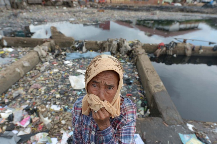 Indonesian Misriati stands next to the Pluit dam, that is full of garbage in Jakarta on January 28, 2013. (Adek Berry/AFP/Getty Images)