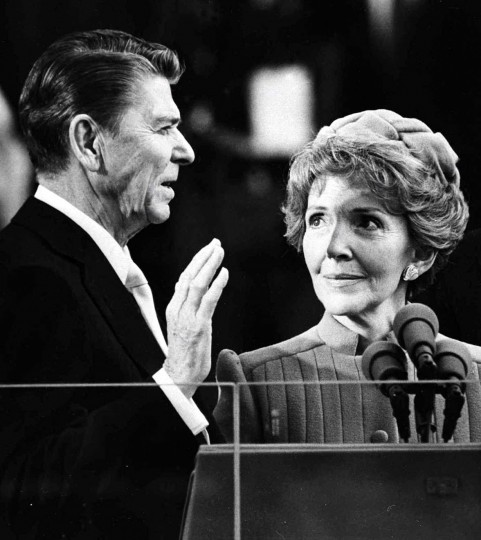 January 20, 1981 — Nancy Reagan watches as her husband Ronald Reagan takes the oath of office at the Capitol January 20, 1981 file photo. (AP File Photo)