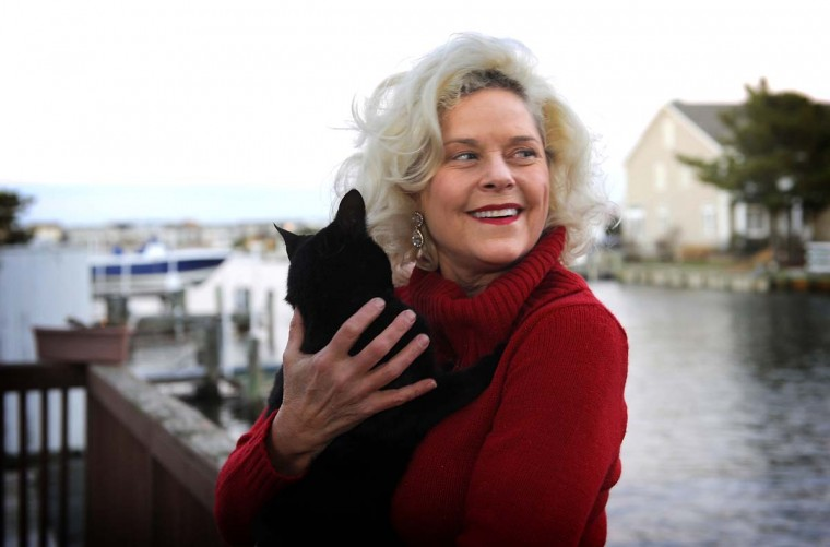 Deborah Lee Walker holds one of several cats she has rescued. She now lives in Ocean City where she's a bank teller and writes a food column. (Barbara Haddock Taylor/Baltimore Sun)