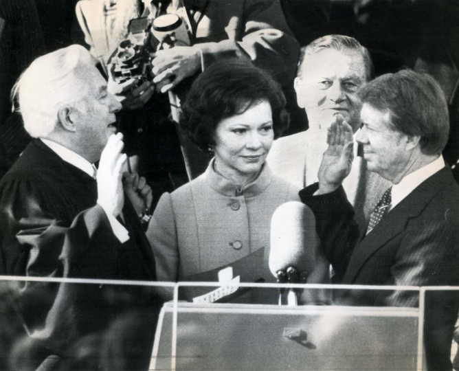 January 20, 1977 — Jimmy Carter takes the oath of office as the 39th president of the United States at the Capitol Thursday as his wife Rosalynn holds the Bible. Chief Justice of the United States Warren Burger administers the oath while Senator Howard Cannon of Nevada stands behind the Carters. (AP File Photo)
