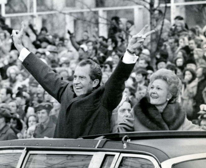 "January 20, 1973 — President Richard M. Nixon extends his arms and fingers in a ""V"" sign as his wife smiles happily at his side in limousine bearing them along the inaugural parade route Saturday. (AP File Photo)"