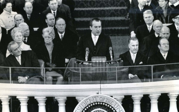"January 20, 1969 — President Richard M. Nixon dedicates his new administration ""to the cause of peace among nations"" as former President Lyndon Johnson listens to the inaugural speech today. Seated at right is Nixon's Vice President Spiro T. Agnew and former Vice President Hubert Humphrey. Behind Johnson is the wife of Sen. Mike Mansfield and at right of her is the wife of Sen. Everett Dirksen. (AP File Photo)"
