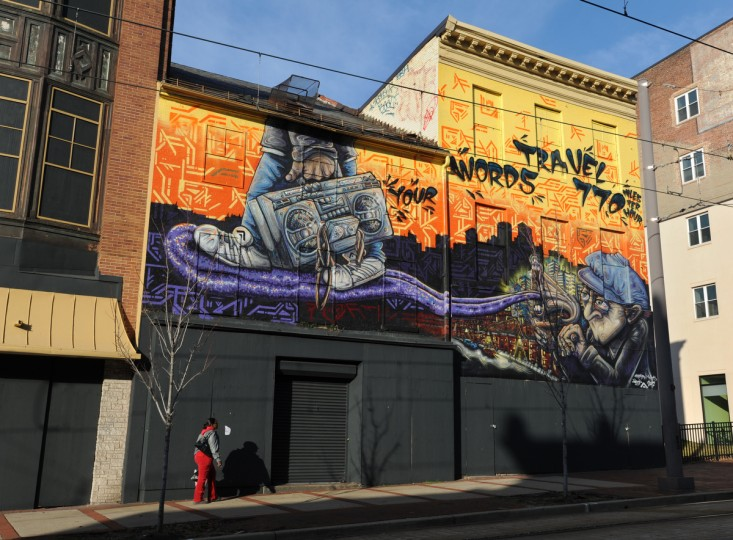 A pedestrian walks past the Ways & J. Digital mural at 414/16 N. Howard St. (Articulate: Baltimore project) (Algerina Perna/Baltimore Sun)