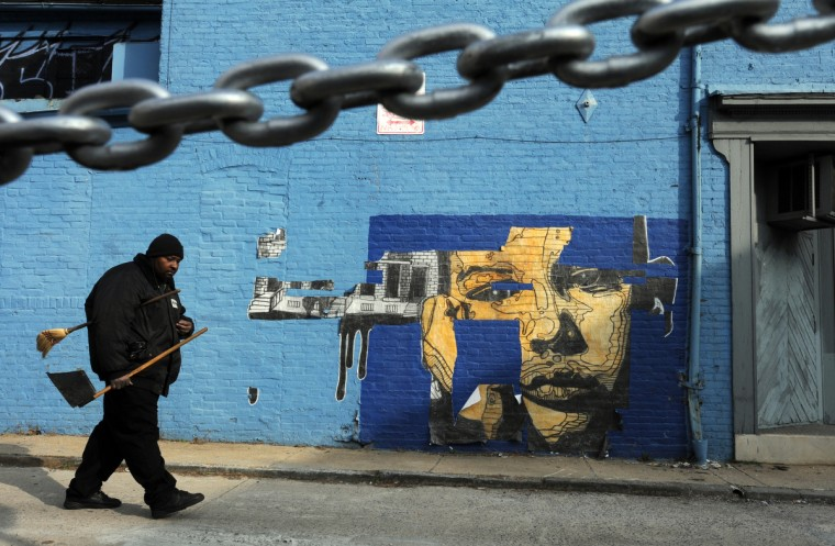 Michael Vinson with Arrow Parking walks by a mural by NETHER on Tyson St. at W. Mulberry Street. (Algerina Perna/Baltimore Sun)