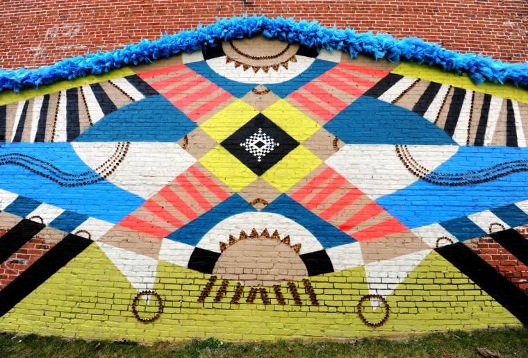 Jesse Unterhalter & Katey Truhn used found objects for their mural: blue shopping bags and bottle caps. It's on the north wall of 416 N. Howard St. (Articulate: Baltimore project) (Algerina Perna/Baltimore Sun)
