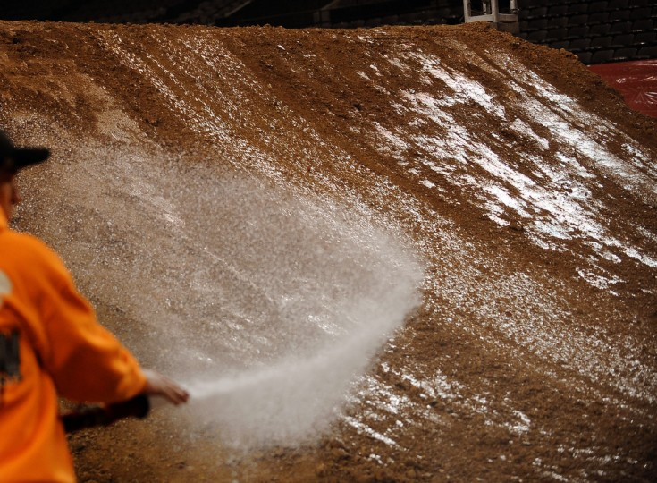 Brion Baker waters the dirt, for compaction purposes, on the high jump leading to the finish line at the 1st Mariner Arena's, Arenacross track built with 1400-1500 cubic feet of dirt. (Gene Sweeney Jr./Baltimore Sun)