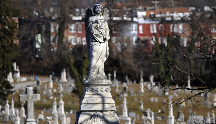 "Carved angels, with their wings and flowing robes are striking figures. On the base of this statue is ""IHS,"" a monogram of the name of Jesus Christ. (Kim Hairston/The Baltimore Sun)"
