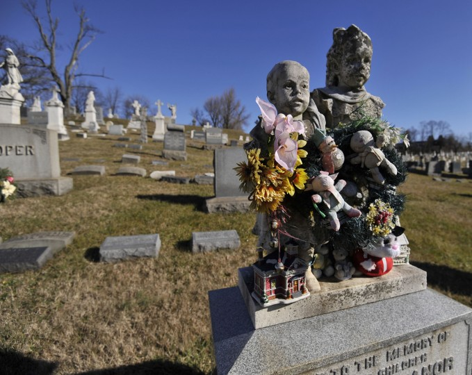 A heavily decorated memorial to two young children is a visible sign that their grave is still visited. (Kim Hairston/The Baltimore Sun)