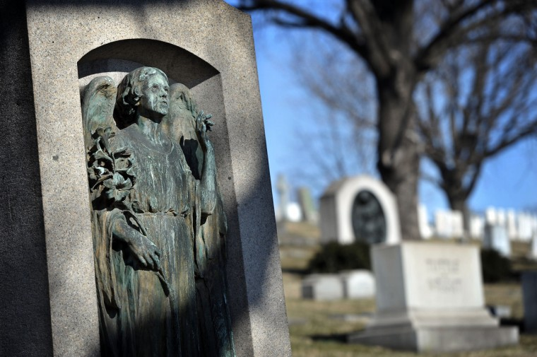 A bronze angel holding a lilly gazes heavenward. (Kim Hairston/The Baltimore Sun)