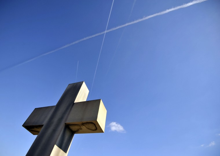 Contrails intersect over a large cross in a cemetery on the east side of the city. (Kim Hairston/The Baltimore Sun)