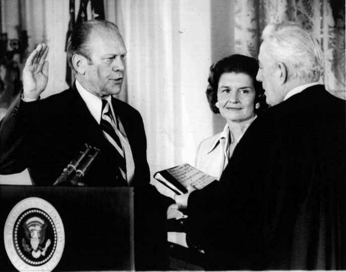 August 9, 1974 —Gerald R. Ford takes the oath of office as the 38th President of the United States in the East Room of the White House. Mrs. Betty Ford looks on as Chief Justice Warren Burger administers the oath in the same room that only hours before Richard M. Nixon bid farewell to members of his staff. (AP File Photo)