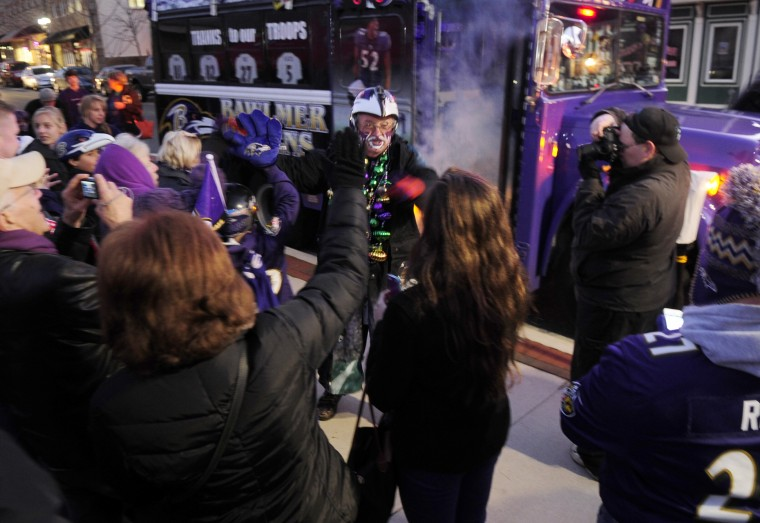 """Fan Man gets the crowd pumped up as he and fellow Bus Boy """"Ravin' Rick"""" Dixon arrive for a Ravens rally at in Bel Air. (Matt Button/Aegis staff)"""