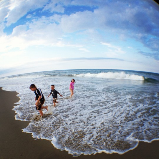 This is a shot of the kids playing in the ocean surf. It was taken in the Outer Banks of North Carolina where we travel every summer on vacation. (Credit: John David Brock)