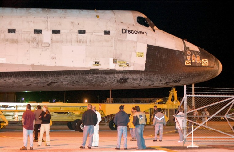 Kennedy Space Center workers look on as Space Shuttle Discovery is moved from the Orbiter Processing Facility to the Vehicle Assembly Building in the early hours of March 29, 2005 at the Kennedy Space Center in Cape Canaveral, Florida. Discovery is scheduled to lift-off May 15, 2005 as the first return to flight mission since the Columbia disaster. (Matt Stroshane/Getty Images)