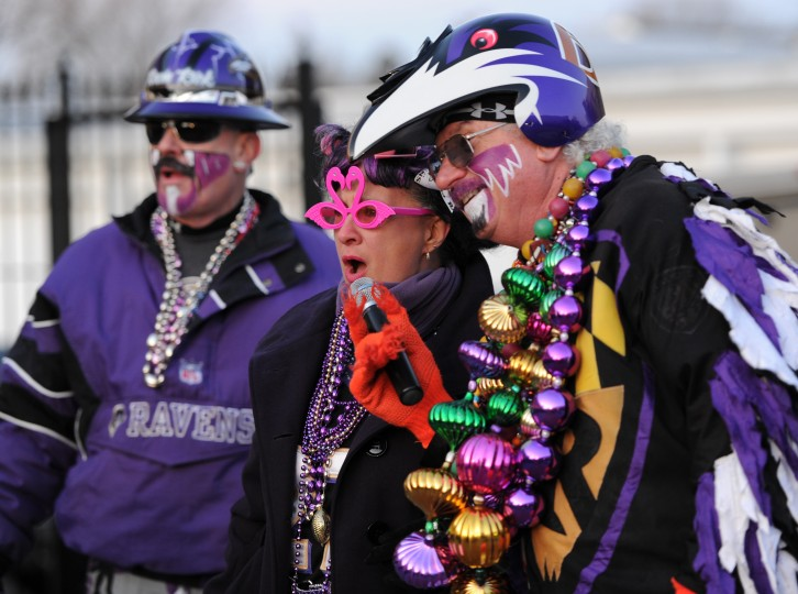 """Lauren Mueller """"Da Ravens Hon"""" tells the crowd what she thinks about the upcoming playoff game on Sunday with Ravin' Rick, right, and Fan Man, left, during a Ravens Rally in Bel Air. (Photo by Nicole Munchel)"""