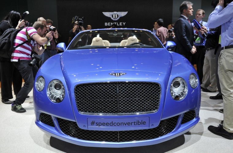 Dr. Wolfgang Schrieber (3rd from R), Chairman and Chief Executive of Bentley, speaks to members of the media next to the Continental GT Speed Convertible as it is unveiled at the North American International Auto Show in Detroit, Michigan. (James Fassinger/Reuters photo)