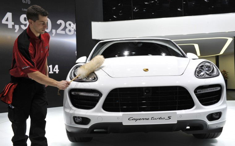 Ken Kozlowski dusts off a Porsche Cayenne Turbo S before the start of the second press day at the North American International Auto Show in Detroit, Michigan. (James Fassinger/Reuters photo)