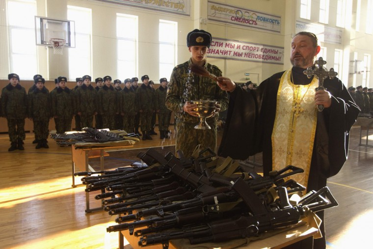 An Orthodox priest blesses rifles during a ceremony where new recruits receive their weapons at a military base of the Belarussian Interior Ministry in Minsk. The traditional ceremony was attended by 325 Belarussian recruits, and it is held a month after the recruits take their military oath. (Vasily Fedosenko/Reuters)