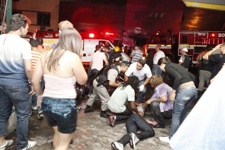 A policeman and rescue workers help a man in front of Kiss nightclub in the southern city of Santa Maria, 187 miles west of the state capital of Porto Alegre, in this picture taken by Agencia RBS, January 27, 2013. At least 200 people were killed in the nightclub fire in southern Brazil on Sunday after a band's pyrotechnics show set the building ablaze, and fleeing patrons were unable to find the emergency exits, local officials said. (Germano Roratto/Agencia RBS via Reuters)