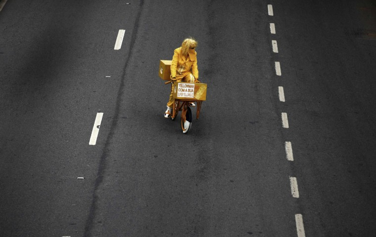 A cyclist rides along Marginal Pinheiros during the World Bike Tour in Sao Paulo, Brazil. The event involves 8,000 people that will ride their bicycles for a better quality of life, according to the organizers. The words on the box reads 'Yellow Man with his Yellow Bike.' (Nacho Doce/Reuters)