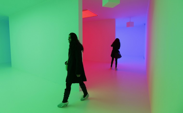 """Visitors wear protective coverings on their shoes as they walk through a light installation called """"Chromosaturation"""" from 1965-2012 by Carlos Cruz-Diez at an exhibition entitled """"Light Show"""" at the Hayward Gallery in London. (Suzanne Plunkett/Reuters)"""