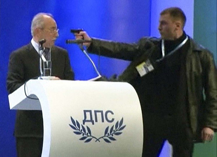 An unidentified man (R) attacks Ahmed Dogan, leader of Bulgaria's Movement for Rights and Freedom (MRF) party, as he delivers his speech during his party's annual conference at the National Palace of Culture in Sofia in this still image taken from video footage on January 19, 2013. Dogan was attacked by a man carrying a gun during his speech at the party conference in Sofia on Saturday. The attacker was later arrested and Dogan escaped unhurt. Video taken January 19, 2013. (BTV via Reuters)