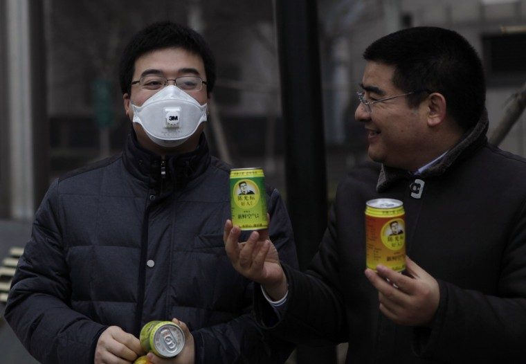 Chinese multimillionaire Chen Guangbiao (R) gives a can of fresh air to a man wearing a mask on a hazy day in central Beijing. China's foulest fortnight for air pollution in memory has rekindled a tongue-in-cheek campaign by a Chinese multimillionaire with a streak of showmanship who is raising the alarm by selling canned fresh air. Chen, who made his fortune in the recycling business and is a high-profile philanthropist, on Wednesday handed out soda pop-sized cans of air, purportedly from far-flung and pristine regions of China, from Xinjiang in the far northwest to Taiwan off China's southeast coast. (Barry Huang/Reuters)