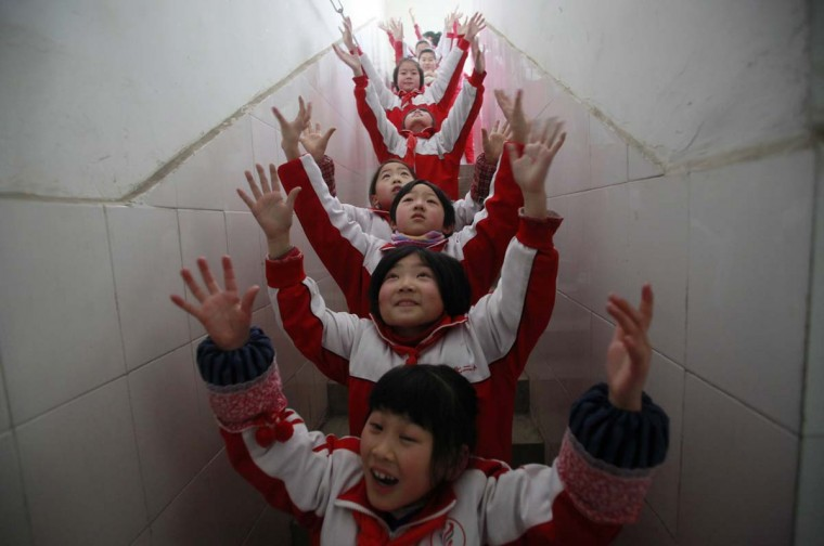 Students do body exercise during class break in a classroom building on a foggy day in Jinan, Shandong province, January 14, 2013. Heavy fog enveloped a large swathe of east and central China, with the city's residents being advised to stay indoors to avoid the heavily polluted air, Xinhua News Agency reported. (China Daily via Reuters)