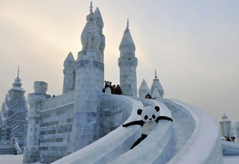An employee wearing a panda costume slides down from an ice sculpture during the Harbin International Ice and Snow World festival in Harbin, Heilongjiang province, China. (Sheng Li/Reuters)
