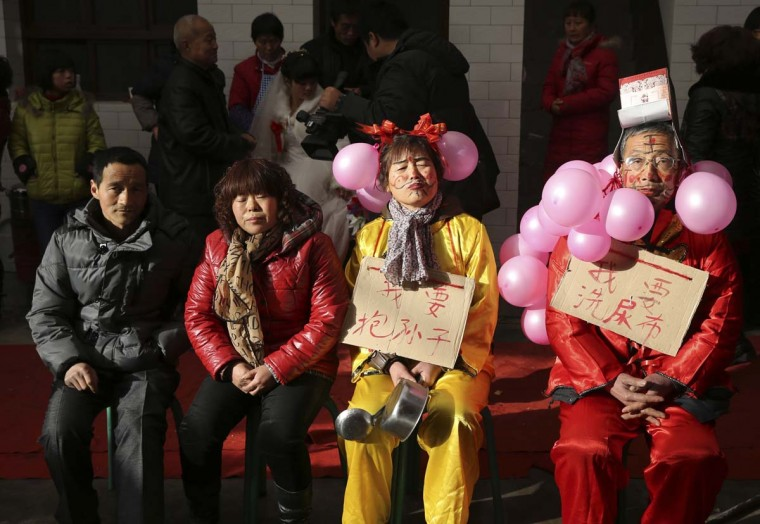 "Parents (R and 2nd R) of a newly married groom wear costumes and make-up, in accordance to a local custom, as they sit next to the parents of the bride in Liquan county of Xianyang city, Shaanxi province, January 1, 2013. The custom, called ""Nao Gong Po"" in Chinese, teases the groom's parents by having them wear ugly costumes and make-up in the belief it helps them improve their affinity with others. The Chinese characters on the placards read, ""I want to have a grandson"" (L) and ""I want to wash diapers"" (R). The bride is seen at the back. Picture taken January 1, 2013. (Rooney Chen/Reuters)"