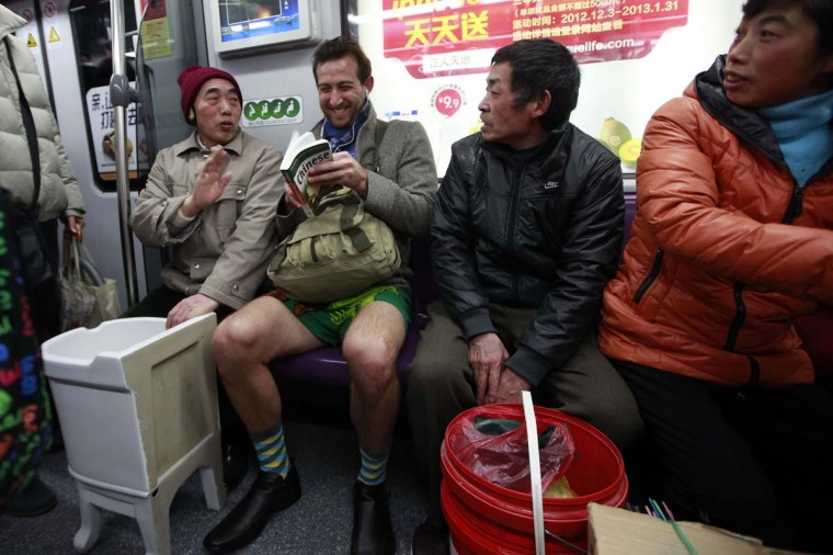 "Passengers react to seeing a man without his pants on the subway during the annual ""No Pants Subway Ride"" in Shanghai January 13, 2013. The event, organised by performance art group Improv Everywhere, involves participants who strip down to their underwear as they go about their normal routine. (Aly Song/Reuters)"