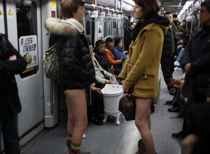 "Passengers look at two women without their pants on the subway during the annual ""No Pants Subway Ride"" in Shanghai January 13, 2013. The event, organised by performance art group Improv Everywhere, involves participants who strip down to their underwear as they go about their normal routine. (Aly Song/Reuters)"