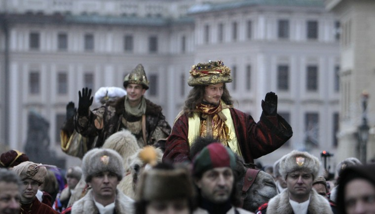 Men dressed as King Caspar, right, and Melchior greet spectators while riding camels during the Three Kings procession at Hradcanske Square as part of a re-enactment of the Nativity scene, in Prague. (David W Cerny/Reuters)