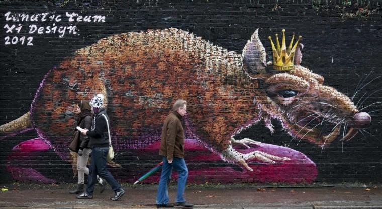 People walk in front of a mural of a rat on a wall in Berlin. (Pawel Kopczynski/Reuters)