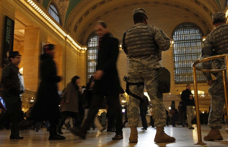 Members of the National Guard watch as commuters move through the main concourse of Grand Central Terminal in New York, January 25, 2013. (Brendan McDermid/Reuters)