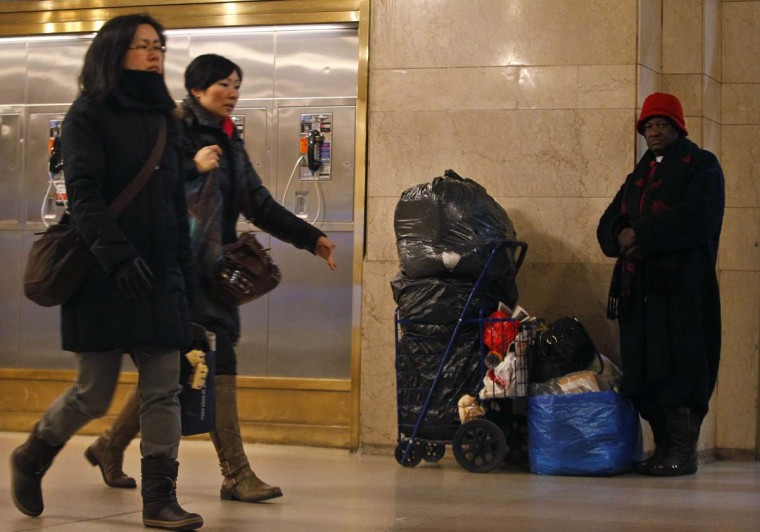 Commuters pass by a homeless person in Grand Central Terminal in New York, January 25, 2013. (Brendan McDermid/Reuters)