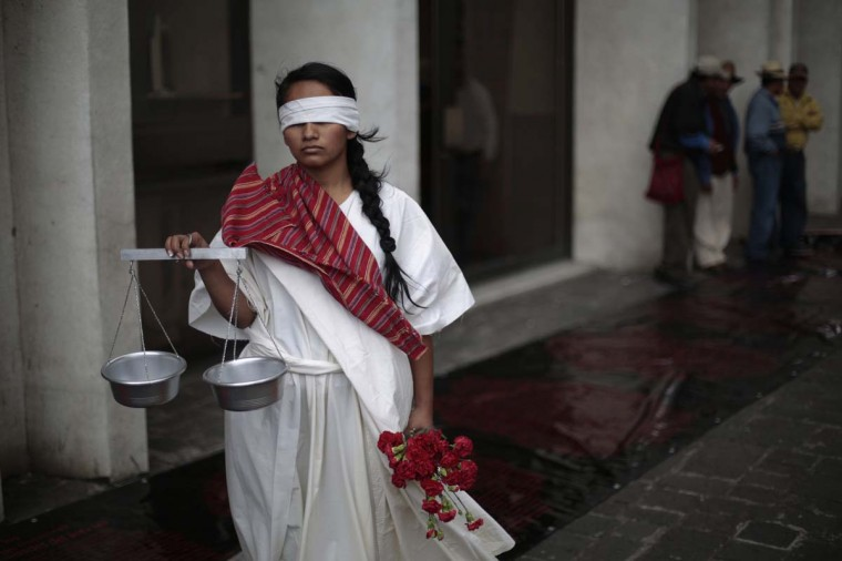A woman, dressed as Lady Justice, stands while protesting at the entrance of the Supreme Court of Justice before former Guatemalan dictator Efrain Rios Montt's hearing in Guatemala City, January 28, 2013. A judge will announce the decision if Rios Montt, who ruled the country from 1982-1983 during a bloody civil war, will be prosecuted on January 28 on genocide charges for the slaughter of the Maya-Ixil ethnic group in the Quiche region in 1982, local media reported. (Jorge Dan Lopez/Reuters)