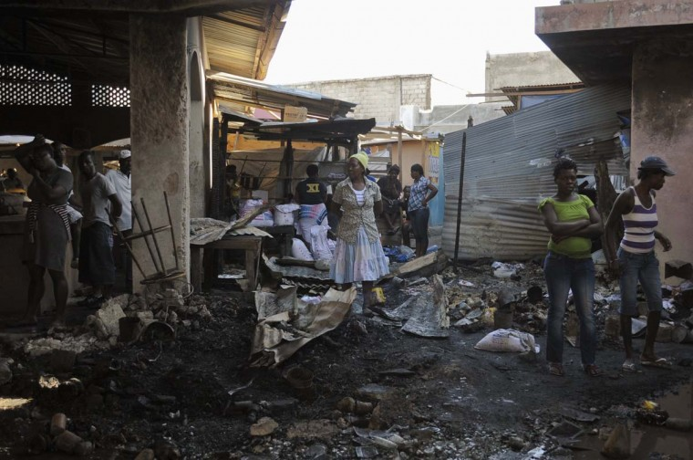 Haitian merchants survery the damage at Mache Public De Tabarre, a public market, after a fire in Port-au-Prince January 6, 2013. The fire, which according to officials, was started deliberately, damaged more than 85 percent of the market and affected jobs, in the Caribbean nation where 78 percent of the population live on less than $2 a day. (Swoan Parker/Reuters)