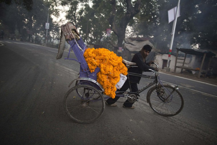 A man transports garlands of marigold flowers on a trishaw along the banks of the Ganges river ahead of the 'Kumbh Mela' (Pitcher Festival), in the northern Indian city of Allahabad, India. During the festival, Hindus take part in a religious gathering on the banks of the river Ganges. 'Kumbh Mela' will return to Allahabad in 12 years. (Ahmad Masood/Reuters)