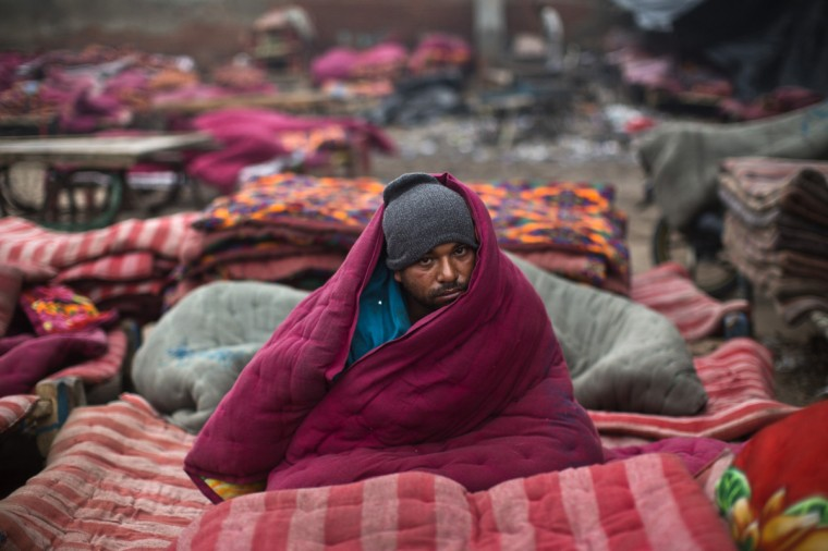 A homeless man, wrapped in a quilt, sits in an open space on a cold winter morning in the old quarters of Delhi. Heavy fog and a cold wave in Northern India have disrupted life in a number of cities, killing scores of homeless in the state of Uttar Pradesh, as the temperature dipped to around 4 degrees Celsius. (Ahmad Masood/Reuters)